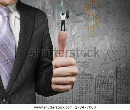 Businessman cheering on top of another big thumb with business concept doodles wall background - stock photo