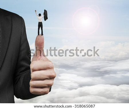 Businessman cheering on top of another big thumb, with sun sky clouds background. - stock photo