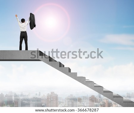 Businessman cheering on top of concrete stairs with city view in sunny day - stock photo