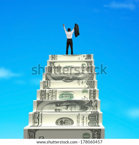 Businessman cheering on top of money stairs with blue sky background - stock photo