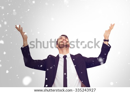 Businessman cheering with hands raised against snow - stock photo