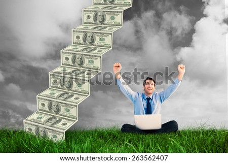 Businessman cheering with laptop sitting on floor against green grass under grey sky - stock photo