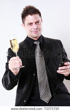 Businessman cheers with his cellphone in one hand - stock photo