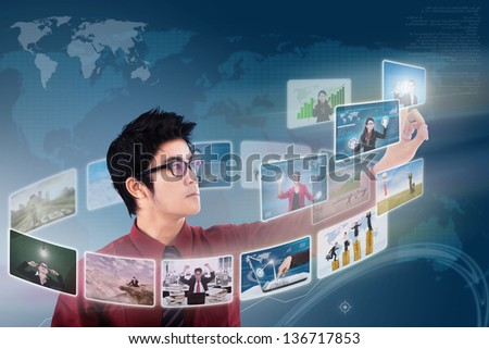 Businessman choosing on photo via digital touchscreen with world map background - stock photo