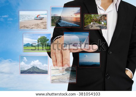 Businessman choosing photo, on digital touchscreen, travel concept and flashback to the past concept - stock photo