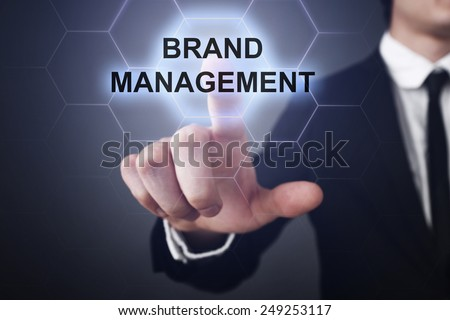 businessman clicks on virtual touchscreen display and select brand management - stock photo
