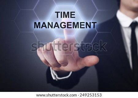 businessman clicks on virtual touchscreen display and select time management - stock photo
