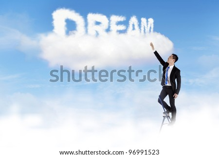 Businessman climbing ladder to fulfill his dream - stock photo