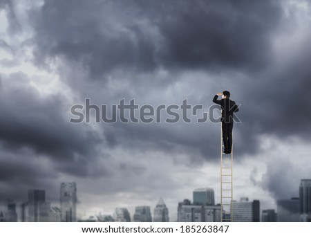 Businessman climbing on a ladder over a city looking ahead - stock photo