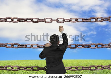 Businessman climbing on old iron chains to go out with natural sky clouds grass background - stock photo