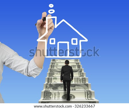 Businessman climbing the money stairs toward white house shape cloud with Female hand holding pen drawing, on blue sky background. - stock photo