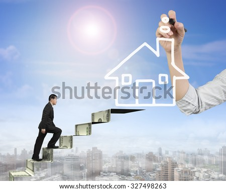Businessman climbing the money stairs toward white house shape cloud with Female hand holding pen drawing, on sun sky cityscape background, side view. - stock photo