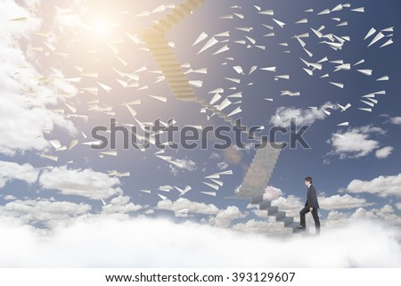 Businessman climbing upstairs, blue sky and paper planes at background. Concept of career growth. - stock photo