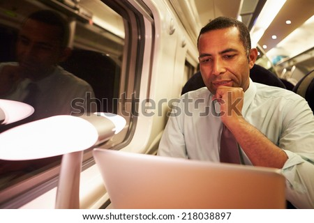 Businessman Commuting To Work On Train And Using Laptop At Night - stock photo