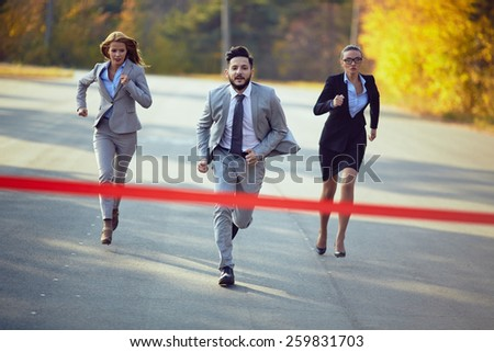 Businessman competing with two businesswomen - stock photo