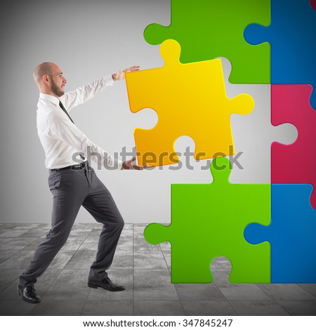Businessman complete a puzzle inserting last piece - stock photo