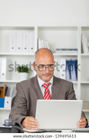 businessman concentrated on his laptop in the office - stock photo