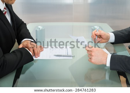 Businessman Conducting An Employment Interview With Application Form On Office Desk - stock photo