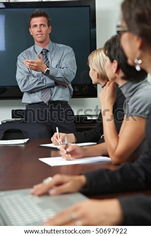 Businessman conducting business training, people sitting in a row, listening. - stock photo
