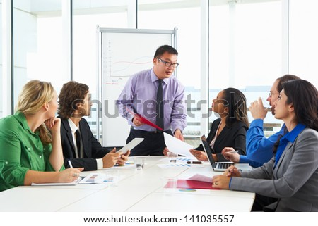 Businessman Conducting Meeting In Boardroom - stock photo