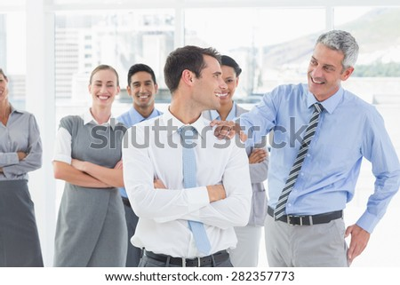 Businessman congratulating his colleagues in office - stock photo