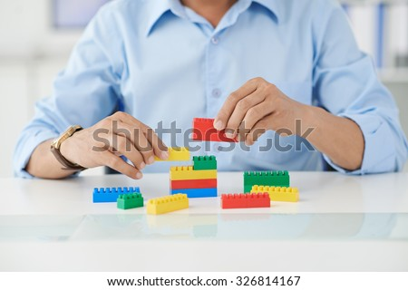 Businessman connecting lego details at his place of work - stock photo