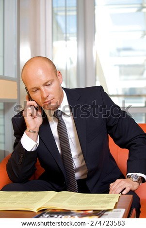 Businessman conversing on mobile phone while reading newspaper - stock photo