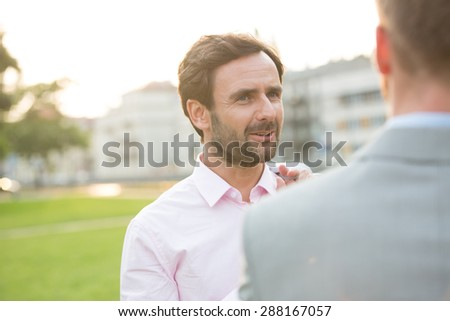 Businessman conversing with colleague at park on sunny day - stock photo