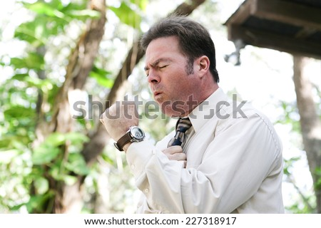 Businessman coughing from the flu, a cold, or other illness, in outdoor environment.   - stock photo