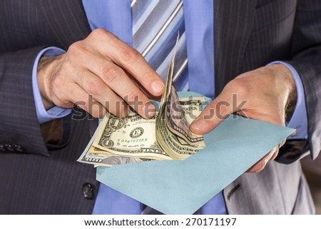 Businessman counting dollars bribe in a blue envelope - stock photo