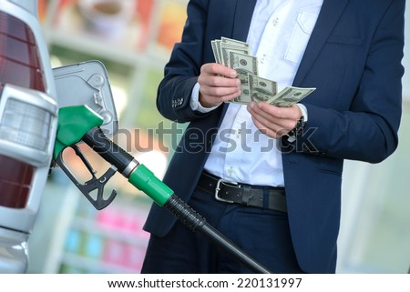 Businessman counting money with gasoline refueling car at fuel station - stock photo
