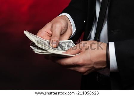 Businessman counts money in hands. - stock photo