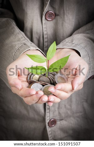 Businessman cover growing plant with coin money - stock photo