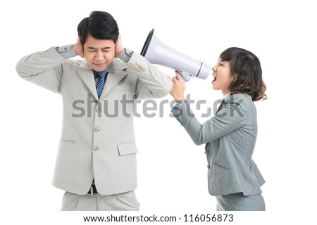 Businessman covering his ears to protect himself from his colleague shouting through loudspeaker - stock photo