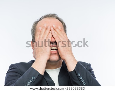 Businessman covering his face with both hands - stock photo