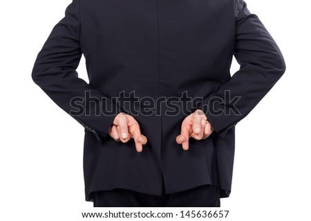 Businessman crossing his fingers behind his back as he embarks on a shady deal or in a gesture of hope isolated on white, cropped view - stock photo
