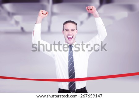 Businessman crossing the finish line and cheering against white abstract room - stock photo