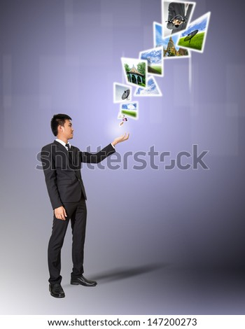 Businessman discharge image from hand to air - stock photo