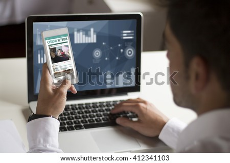 businessman distracting at work with smartphone showing social network on screen. All screen graphics are made up. - stock photo