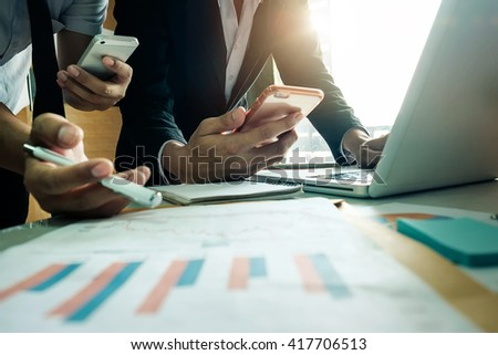 businessman documents on office table with smart phone and laptop and two colleagues discussing data in the background in morning light - stock photo