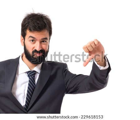 Businessman doing a bad signal over white background - stock photo