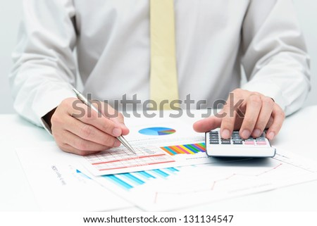 Businessman doing business financial analysis with calculator - stock photo