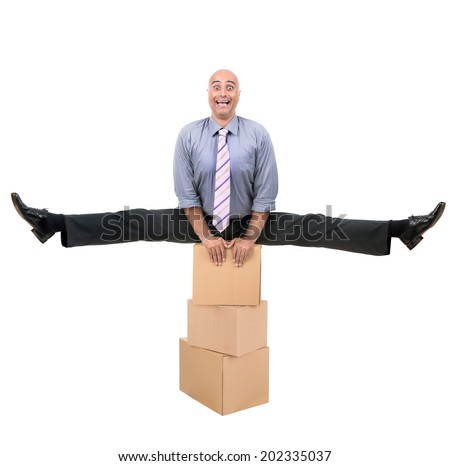 Businessman doing exercises over a stack of cardboard boxes - stock photo