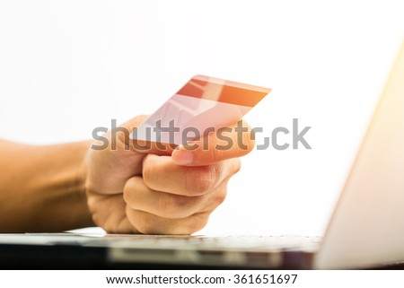 Businessman doing online banking, online shopping, making a payment or purchasing goods on the internet entering his credit card details on a pc, close up view of his hands. Vintage filter - stock photo