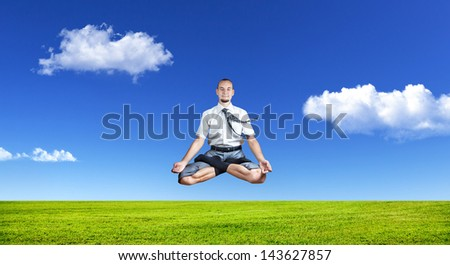 Businessman doing Yoga meditation and levitating under the grass at blue sky with white clouds - stock photo
