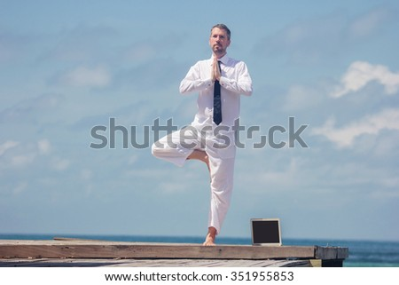 businessman doing yoga on a wooden bridge with a laptop - stock photo