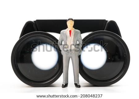 Businessman doll stand on top of binoculars in cocept show vision - stock photo