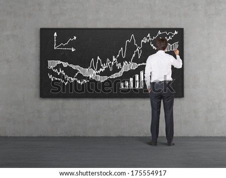 Businessman drawing a chart on the blackboard - stock photo
