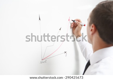 Businessman drawing a graph on a whiteboard - stock photo