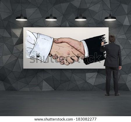 Businessman drawing a handshake sketch - stock photo
